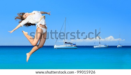 Beautiful young sexy woman jumping on the beach