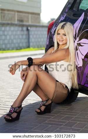Beautiful young sexy woman near car outdoor. Rich hot blond slim girl with long healthy hair posing with luxury expensive automobile. Fashion model spring-summer
