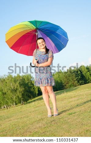 Beautiful young sexy woman posing on nature with color umbrella - stock photo