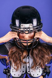 Beautiful Young Sexy Woman wearing American Football Uniform with Ball on a blue background. Studio photo of american football woman.