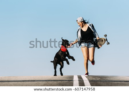 Beautiful young skater playing with her dog in the city.