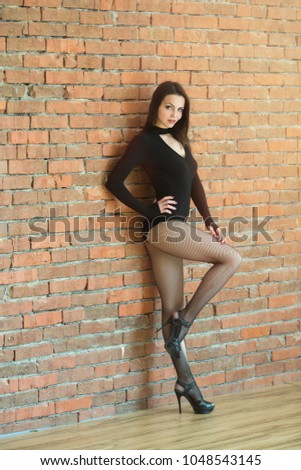 beautiful young slender girl in black bodie standing near a brick wall #1048543145
