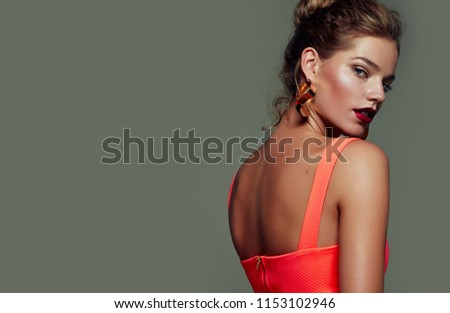 Beautiful young, slender, tanned girl with bright make-up and high hairstyle posing in the studio in a fashionable dress on a gray background.