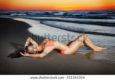 beautiful young slim girl lying down on sand at the water