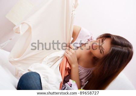Beautiful young slim woman on the bed indoors unpacking clothes from suitcase