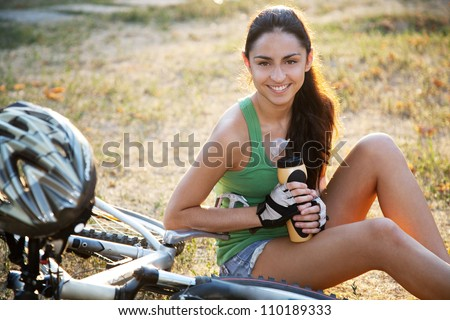 Beautiful young slim woman riding a bicycle