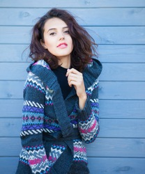 Beautiful young smiling brunette woman with  wearing knitted nordic print cardigan on a grey wooden background. Winter fall fashion concept.