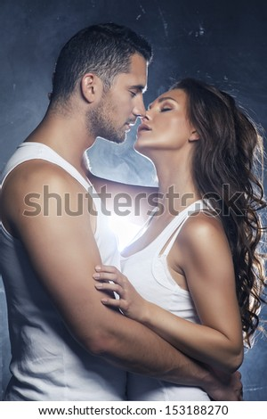 Beautiful young smiling couple in love embracing kissing