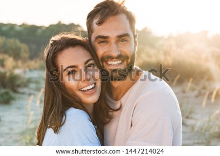 Beautiful young smiling couple spending time at the beach, hugging #1447214024