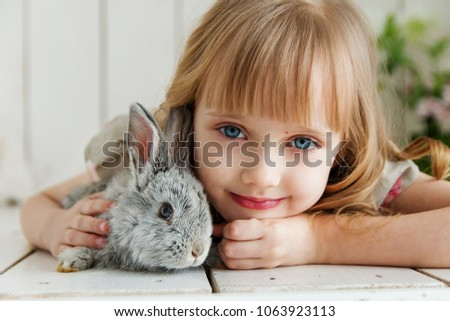Beautiful young smiling  girl is hugging a  little grey rabbit; child and rabbit