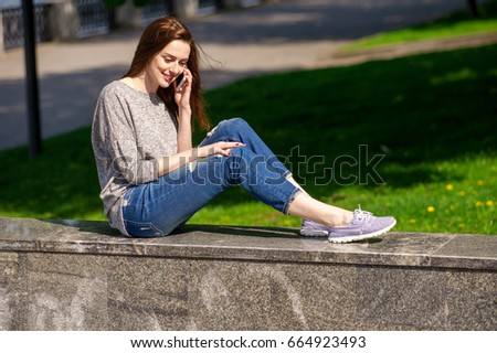Beautiful young smiling girl is sitting on a stone parapet and talking on the phone #664923493