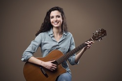 Beautiful young smiling girl playing acoustic guitar