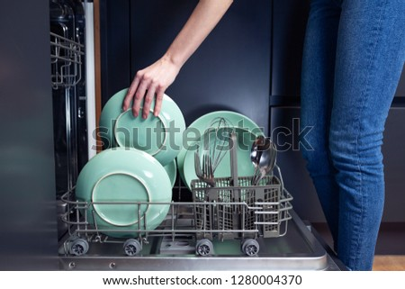 Beautiful young smiling woman doing dishes in a modern kitchen with dishwasher