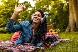 Beautiful young smiling woman lying on a picnic blanket in park and listening to music on smartphone. She is waiting for someone