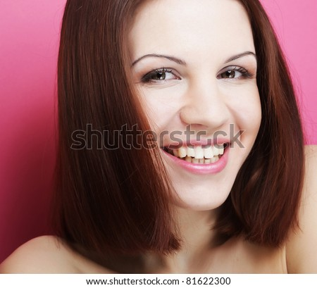 Beautiful young smiling woman with clean skin - over pink background