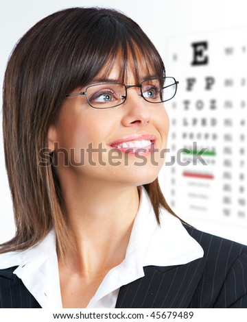 Beautiful young smiling woman with eyeglasses and eye chart - stock photo