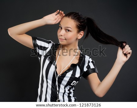 Beautiful young Soccer referee at black background