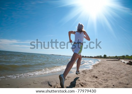 Beautiful young sport woman running in sea coast on sunny summer day