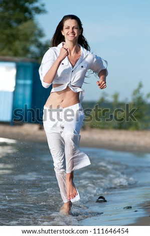 Beautiful young sport woman running on water at sea coast