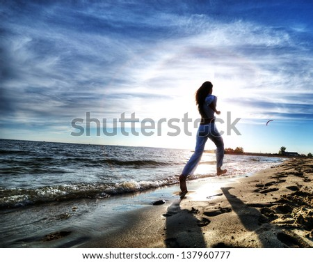 Beautiful young sport woman running on water at sea coast. Sunset with dramatic sky