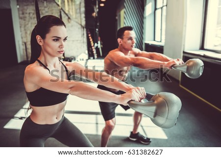 Stock Photo Beautiful young sports couple is working out with kettlebell in gym