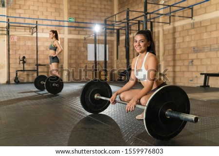 Beautiful young sportswoman crouching with barbell while exercising with friend at health club