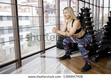 Stock Photo Beautiful young sportswoman standing and doing squats in gym. Active Lifestyle. Sports in the gym.