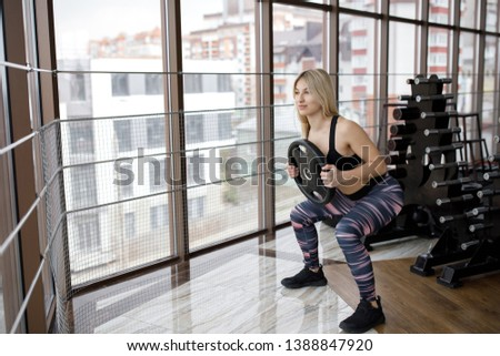 Stock Photo Beautiful young sportswoman standing and doing squats in gym and holding dumbbells for the rod in their hands. Active Lifestyle. Sports in the gym.