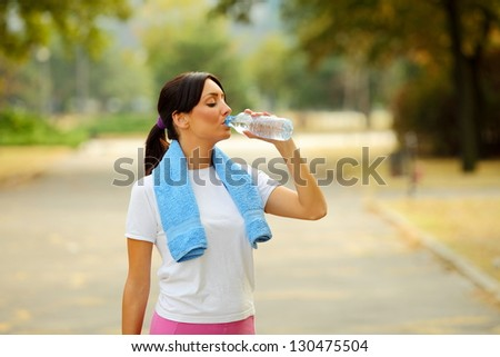 Beautiful young sporty woman with towel around neck drinking water after fitness exercise