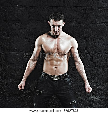 Beautiful young strong man posing on dark background - stock photo