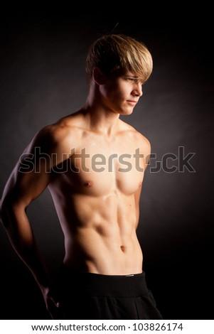 Beautiful young strong man posing on studio - stock photo