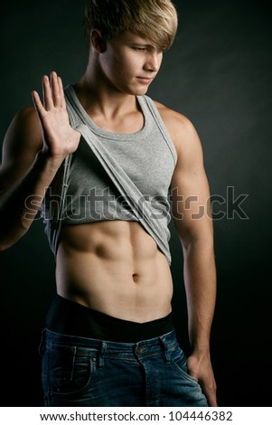 Beautiful young strong man posing on studio