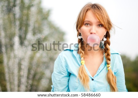 beautiful young student girl blowing bubble from chewing gum and looking into the camera