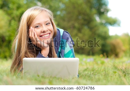 beautiful young student girl lying on grass with laptop and books, looking into the camera and smiling