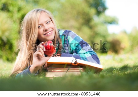 beautiful young student girl lying on grass with red apple in her hand and books under her hands, looking into the camera and smiling