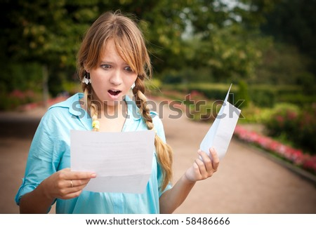 beautiful young student girl shocked by message she is reading. She is standing in campus park, holding paper with message and envelope.