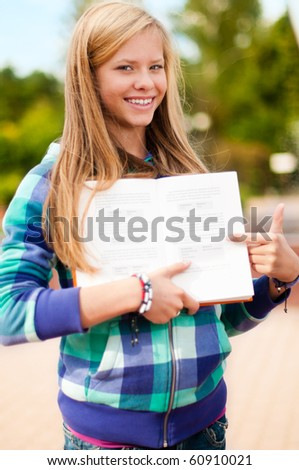 beautiful young student girl standing in park, smiling and looking into the camera, showing you something in book
