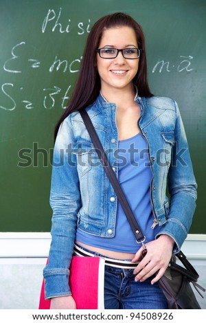 beautiful young student in glasses standing at the blackboard