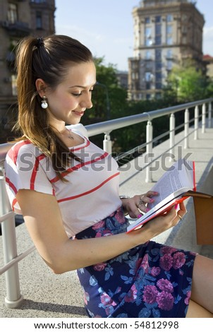 beautiful young student reads the book at sunny day