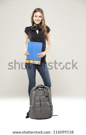 Beautiful young student with school bag and books