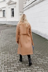 Beautiful young stylish blonde woman wearing long beige coat, grey hat and black boots walking through the city streets. Trendy casual outfit. Street fashion. Back view.