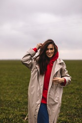 Beautiful young stylish brunette woman wear long beige coat and red hoodie walking through the field. Happy girl. Winter, spring, autumn or fall look. Minimalistic look. Trendy casual outfit.