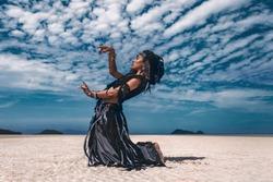 Beautiful young stylish tribal dancer. Woman in oriental costume dancing outdoors