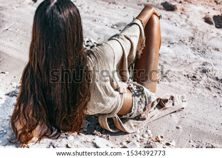 beautiful young stylish woman with stylish boho accessories lying on sand