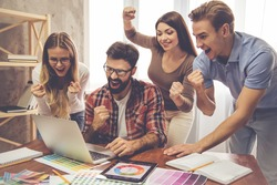 Beautiful young successful designers are raising hands in fists and smiling while working with a laptop in office
