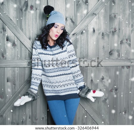 Beautiful  young surprised woman wearing winter hat and gloves covered with snow flakes. Christmas portrait concept.