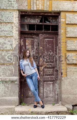 beautiful young sweet girl with red hair in jeans standing near the door of the old city