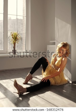 Beautiful young sweet model in yellow and black dress sit on flor and look on shadow  near close white window with green little palm tree and thinking.
