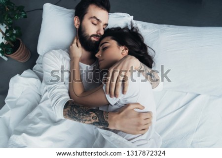 beautiful young tattooed couple embracing while sleeping in bed #1317872324