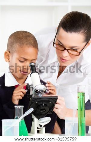 beautiful young teacher helping school boy in science class